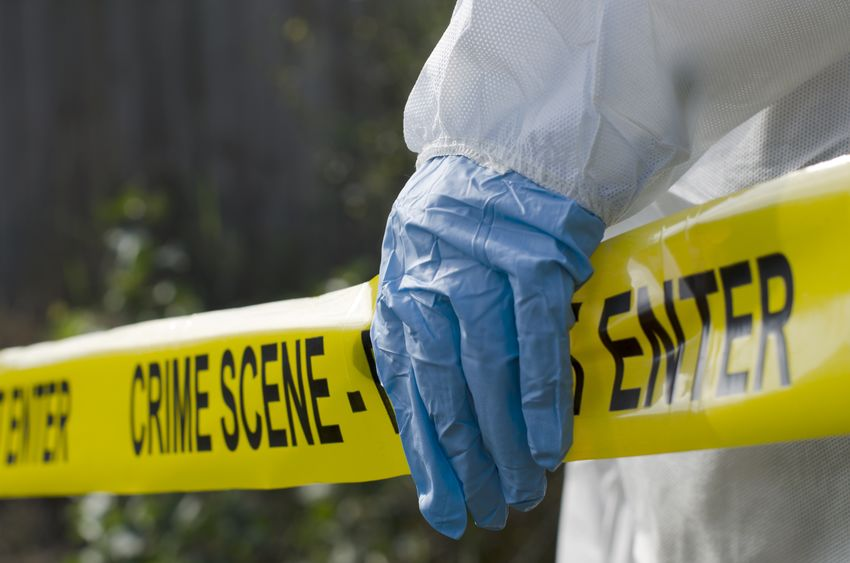 Gloved hand holding Crime Scene tape